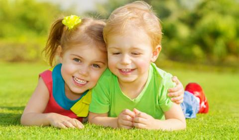 Two young kids smiling at a park in Nashville